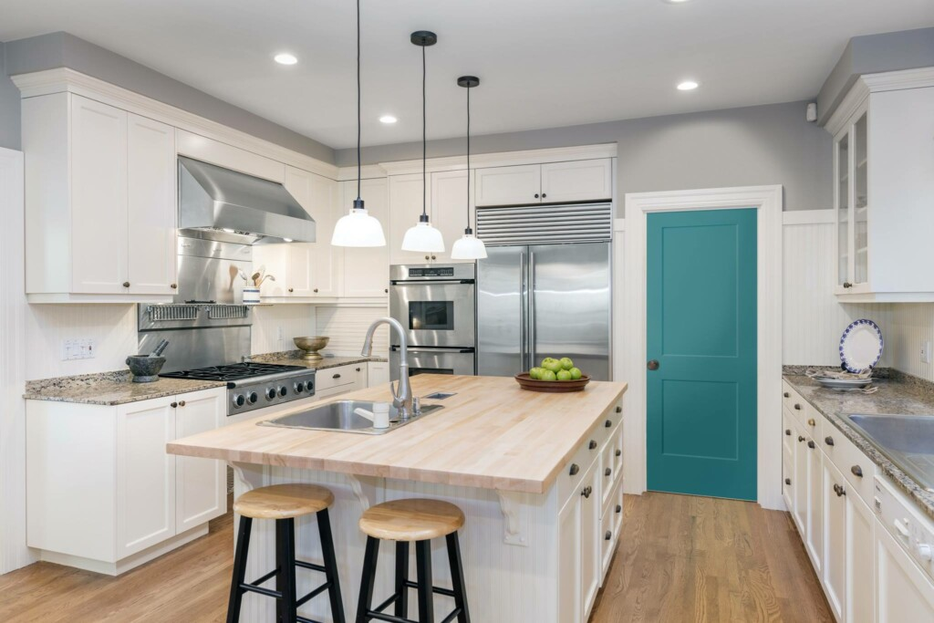 picture of a kitchen that has painted only a small part of it, which is the door, with accent color.