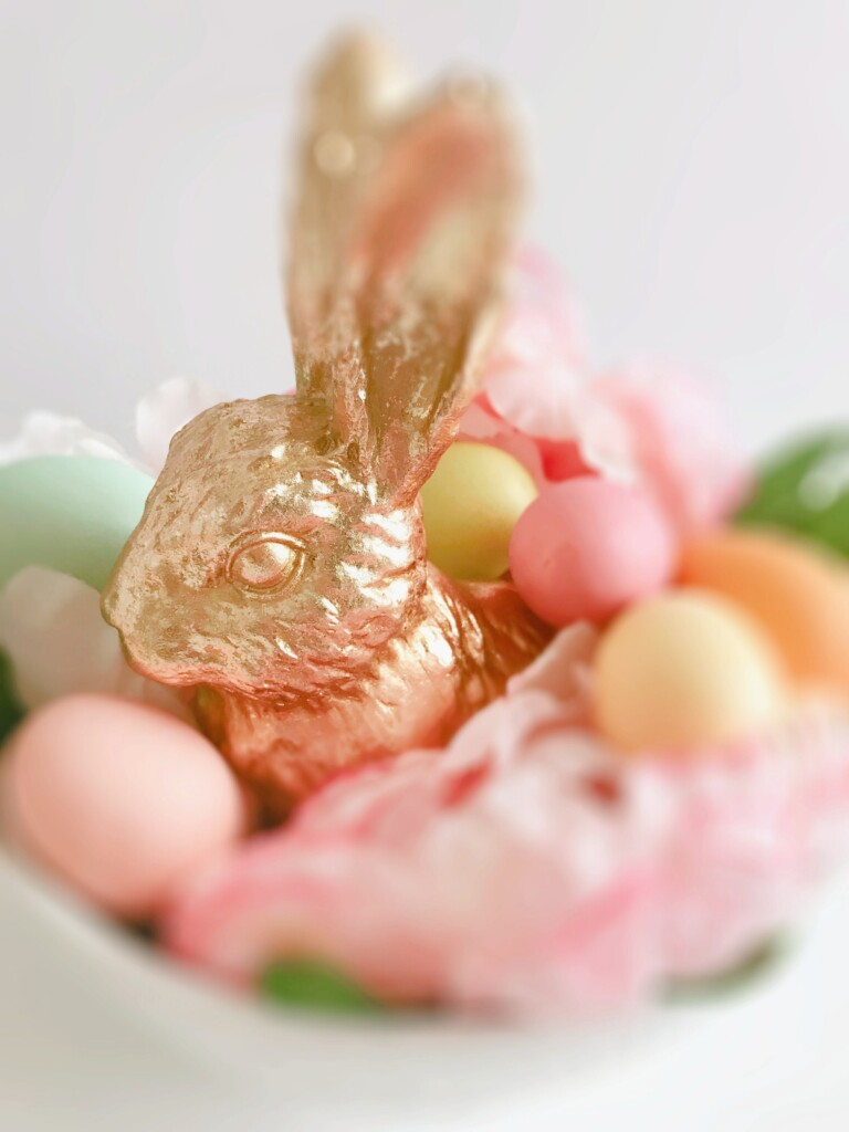 small golden easter rabbit statue in a bowl full of orange and pink eggs and pink flowers