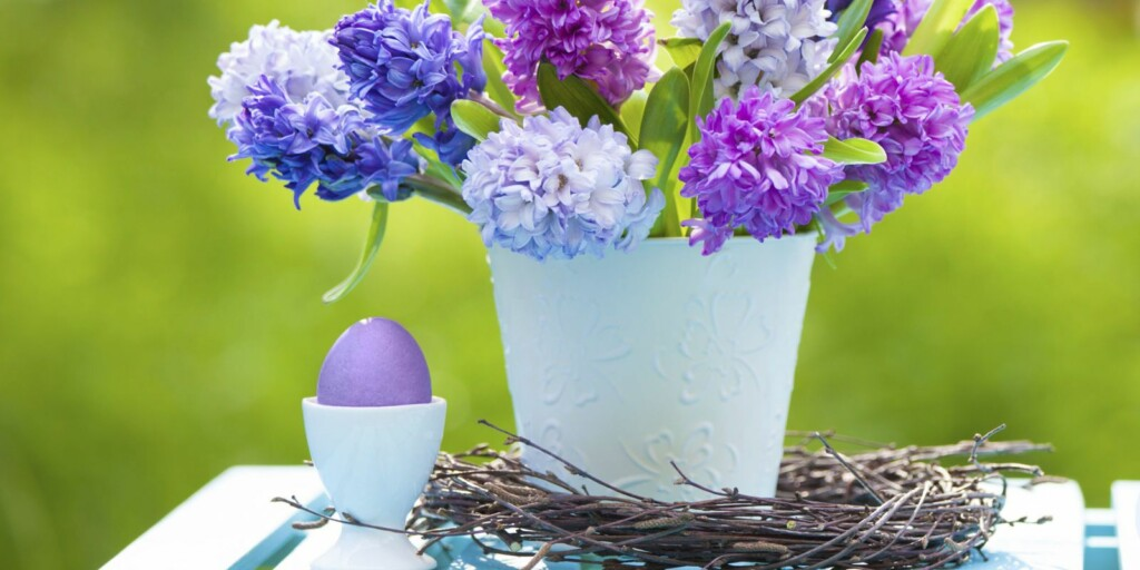 a purple easter egg on the table next to a white vase with purple lavender flowers