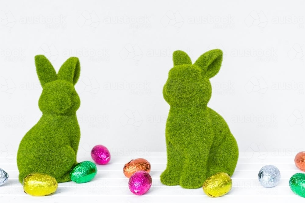 two statues of velvet green rabbits Easter next to colored eggs