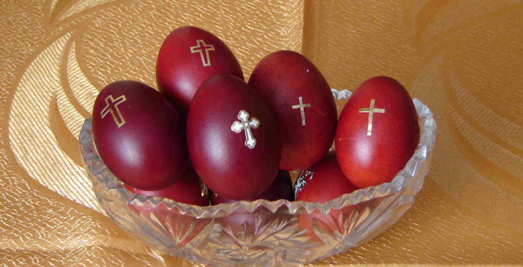 several red eggs with a picture of a cross painted on them in a glass jar