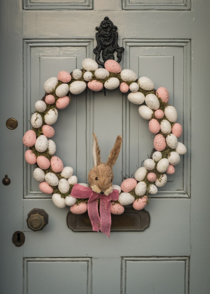 aring made of pink pastel eggs and a rabbit doll with a pink bow tie on the gray door of a house for easter