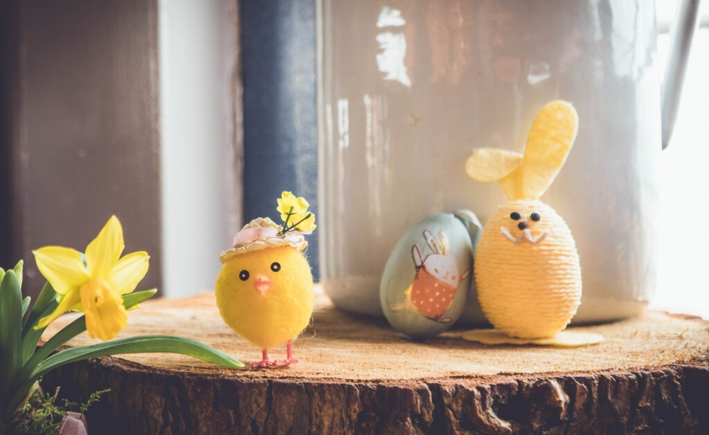 yellow rabbit-painted eggs next to a small doll of a chicken on a piece of wood next to a white vase