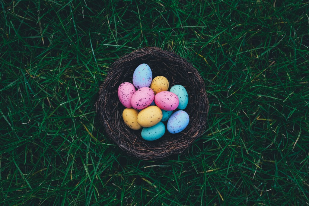 several blue, orange and pink easter pastel eggs in a wooden basket on the grass