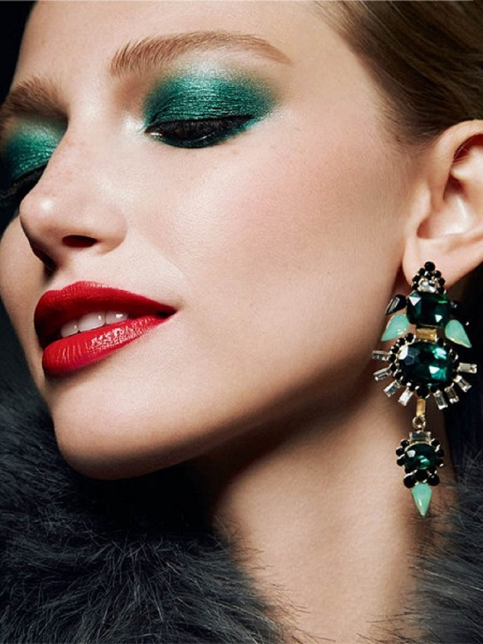 a girl with a green color eyeshadow and red lipstick.