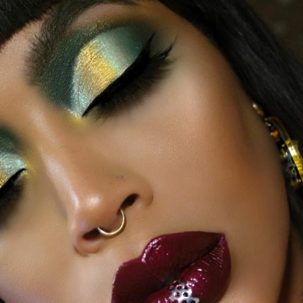 a girl with olive green and gold eyeshadow and crimson lipstick.