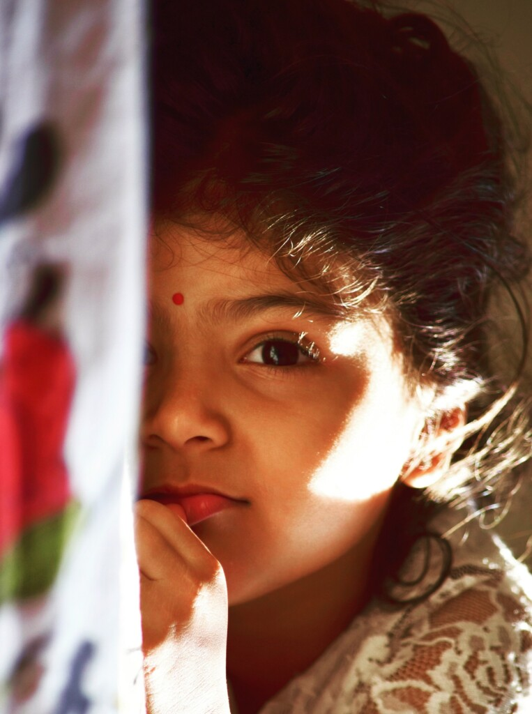 a little girl with a red tilak on her foreheads.