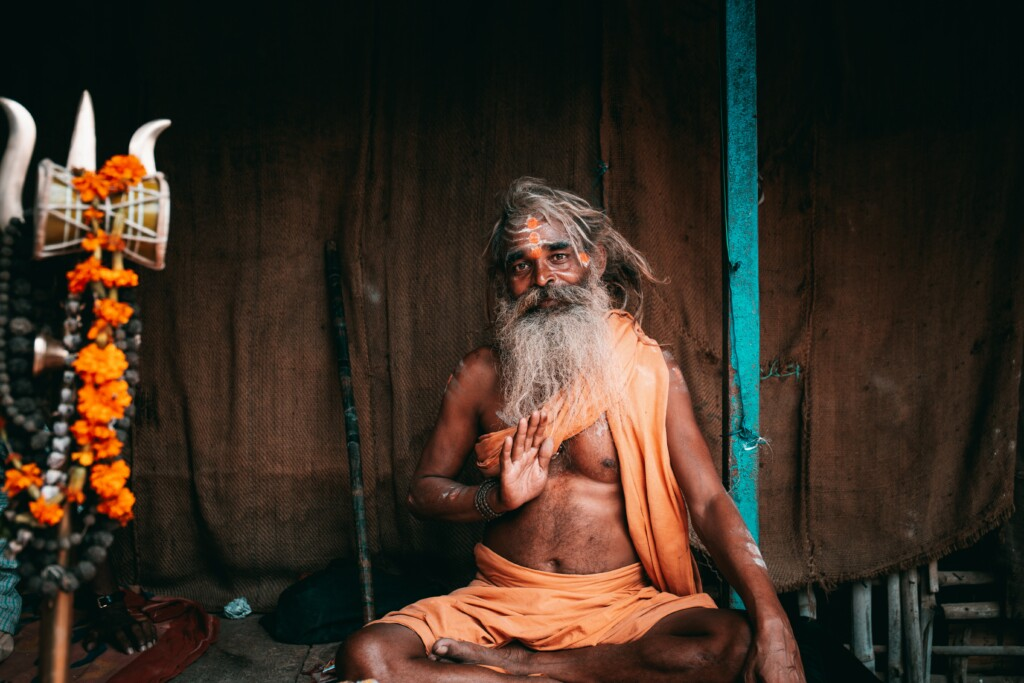 an image of an indian ascetic dressed in orange and his face painted orange.