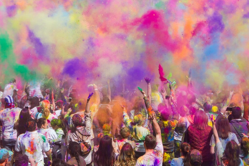 a picture of people throwing colored powders in the sky during Holi celebration.